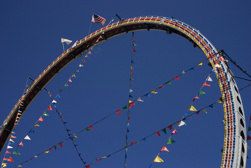 Arched loop of a roller coaster against a blue sky