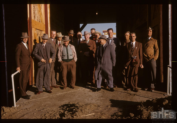 Official opening - new elevator annex [from Gallery showing Shaunavon Summer '03 - front row - man with hands in pocket grey and black sweater/vest - Fletcher Walls.  Middle doorway second row man with shadow on face beige hat - Art Reswick; man on far right - tan sports coat - Vern Cave]. Aneroid. 10/21/1955