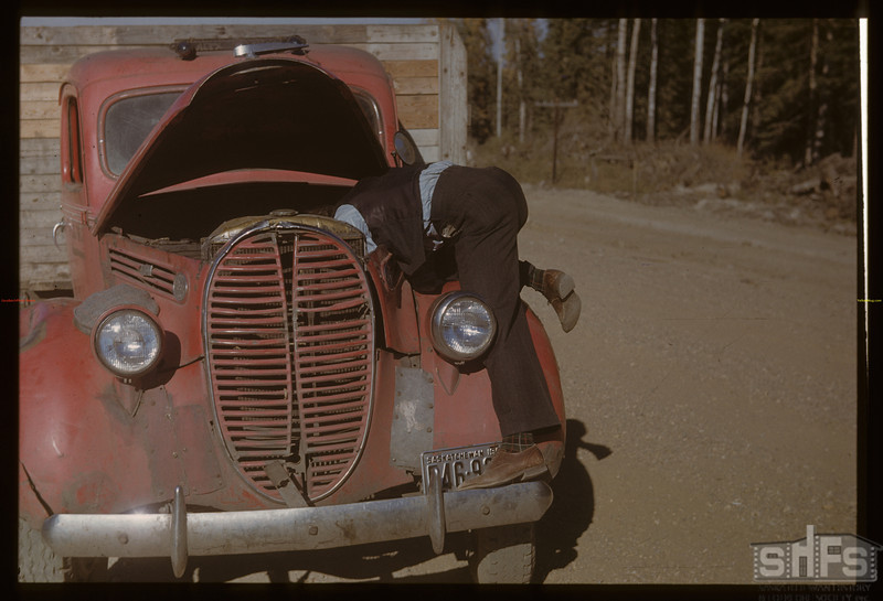 Bruce Buchanan helping with Mike Melinski's truck. Meadow Lake. 10/01/1948