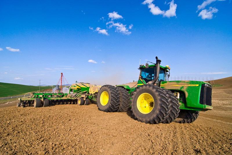 A large tractor pulling an air drill planting crops in the spring in the Palouse region of Washington