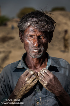 Tough brick kiln laborer posing under harsh sun