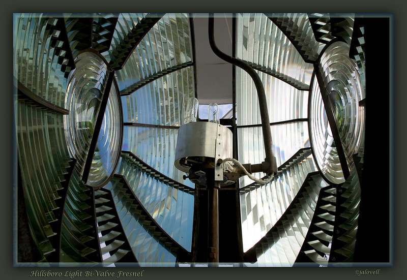 """The Hillsboro Lighthouse is fitted with an original Second Order bivalve Fresnel lens. Manufactured with the encryption: """"Phares & Fanaux, Barbier, Benard & Turenne, 82 Rue Curial, Paris"""", the lens consists of concentric prisms arranged in panels around a central bullseye; its twin halves resembling a bivalve shell.  A mercury float trough was once used but today a ball bearing system in oil supports the 2 and 1/2 ton lens. Known as  the """"big diamond' this light shines 28 nautical miles out to sea. The source of illumination is the twin 1000 watt lamp arrangement shown."""