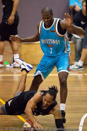 CJ Bruton trips under the defensive pressure of James Maye - Gold Coast Blaze v New Zealand Breakers NBL basketball pre-season game; 4 October 2010, Carrara Stadium, Gold Coast, Queensland, Australia