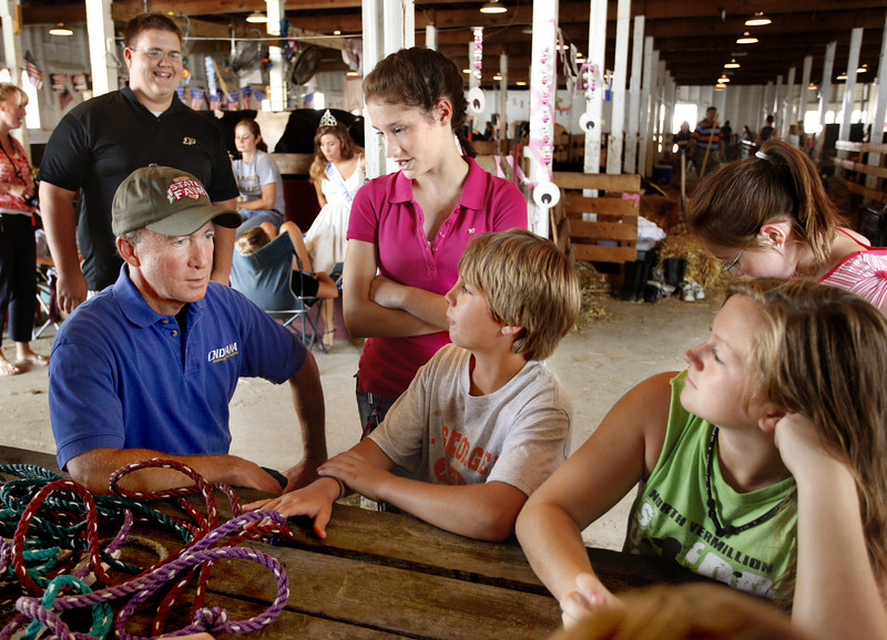 By Alex Turco/Journal & Courier-- Governor Mitch Daniels talks to fair participants (from left) Elizabeth Downard, 15, Daemyn Gott, 12, and Erin Mecklenburg, 14, while James Evans, 18, looks on at the Tippecanoe County Fair in Lafayette on July 23, 2009.