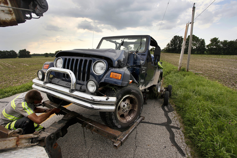By Alex Turco/Journal & Courier-- Tow truck driver Sidney Means works on a Jeep that was abandoned after an accident, that broke a power-pole, about a mile south of Dayton United Methodist in Dayton, on Wednesday, June 24, 2009.