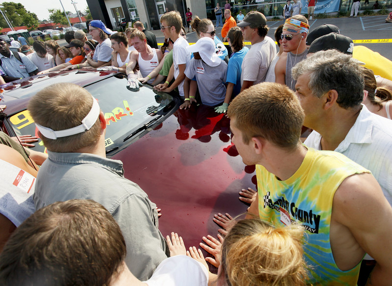 By Alex Turco/Journal & Courier-- Contestants crowd around a '97 Mercury Cougar that is the prize in the Bob Rohrman Lincoln-Mercury dealership's Free Ride contest, Friday, June 26, in Lafayette. The contest challenges participants to be the last one with their hand touching the car.