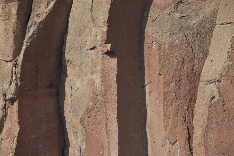 "Segmented walls of Smith Rock State Park contrast the afternoon light with its ""welded tuff"" rock formed from volcanic ash compressed with extreme heat and pressure. This rock is quite solid which makes it great for rock climbing. Here, one can see the pock-marks from multiple ascents."