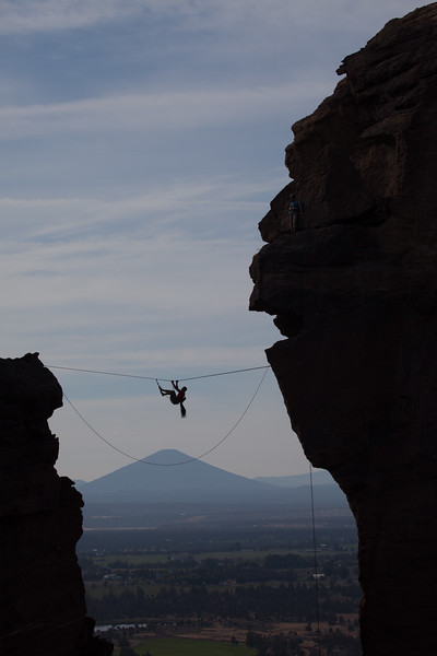 A climber pulls himself across the highline gap between Monkey Face and Misery Ridge in Smith Rock State Park, Oregon.