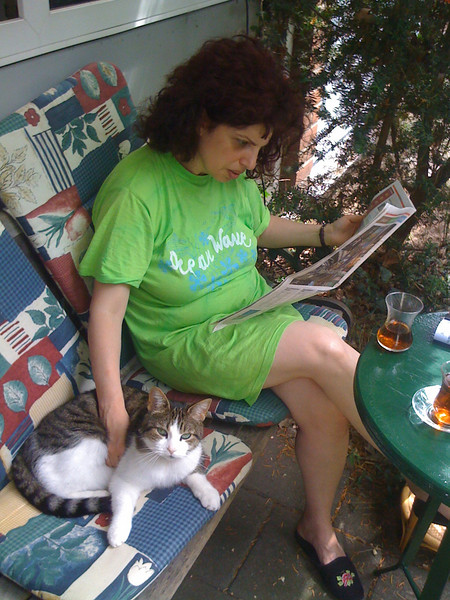 My wife, reading while holding our cat, in front of our house<br /> (Photo taken with my iPhone 3G, and SmugShot automatically sent it to this page!!)
