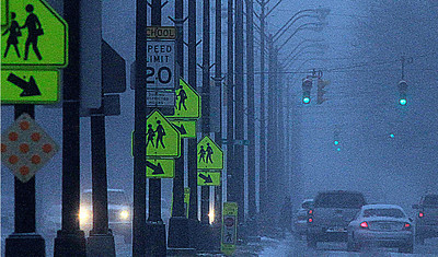 12/12/2010 a lone pedestrian crosses Middle avenue about 6ht street Sunday afternoon in ht gathereing gloom and snow. Photo by Tom Mahl