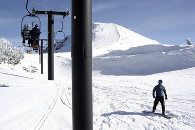 A snowboarder heads below the lift