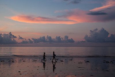 Children collecting crabs and small fish during low tide.  Sabang, Palawan, Philippines