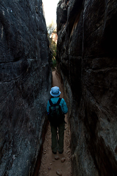Cindy negotiates a narrow, narrow section of the Chesler Park trail in Canyonlands.<br /> Photo © Carl Clark