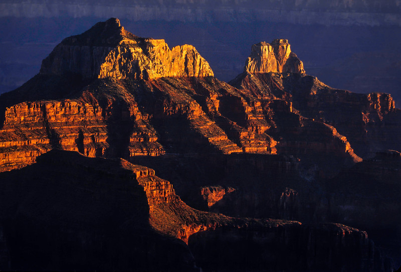 The setting sun fires up these ancient rocks seen from the north rim of the Grand Canyon.<br /> Photo © Cindy Clark
