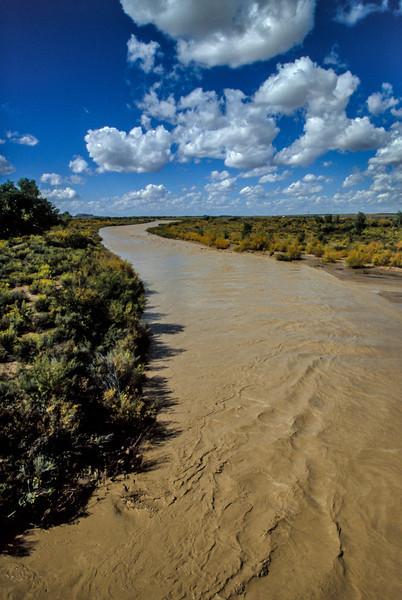 Swollen by autumn rains, a muddy Puerco River flows through the Petrified Forest.<br /> Photo © Carl Clark