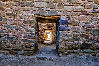 In the ruins at Aztec, New Mexico, the ancient rooms built from colorful rocks lead out through descending doorways.