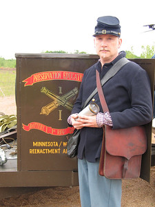 One of the lads displays the projectile that will be used in the canon. Also displayed are the colors of the reenactment regiment.