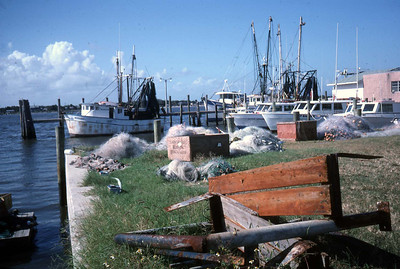 Nets piled by the Mayport docks with docked fishing boats in the background in 1991.