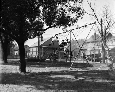 Children playing on swings at the Emerson Street Nursery School in 1935.