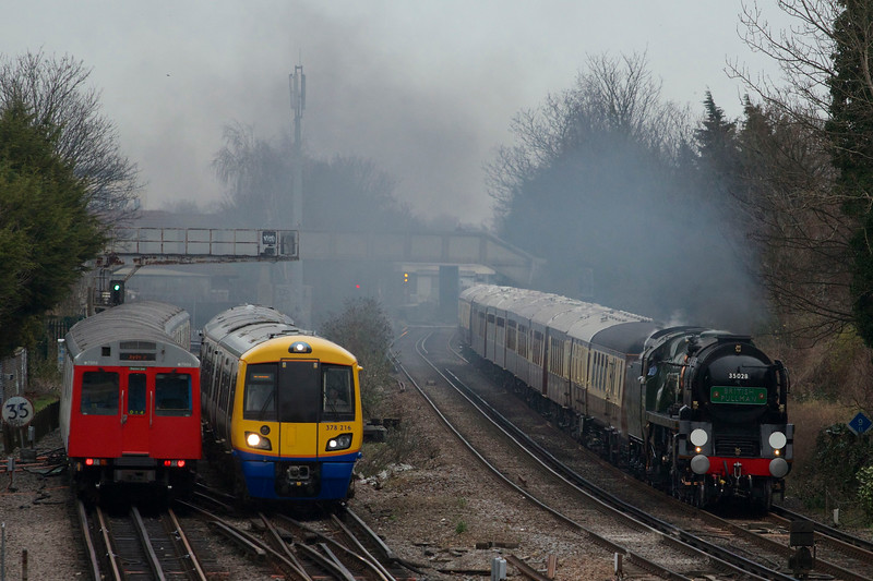 Britain's first mainline steam train excursion of 2014 today (Friday Jan 24): Steam engine Clan Line hauls the VSOE British Pullman - sister train to the Orient Express - through Richmond in Surrey at lunchtime on the outward leg of a round trip from London Victoria to Guildford. Seen here passing a London Underground District Line tube train and a London Overground train. The cost of the afternoon luxury excursion was £395 per person, including a five course lunch with champagne.