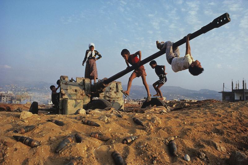 """<font size=""""3""""><font face=""""arial""""> Children clamber over an abandoned anti-aircraft gun near Beirut, Lebanon, 1982"""