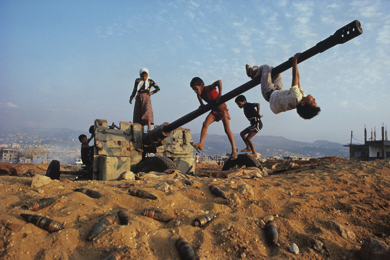 "<font size=""3""><font face=""arial""> Children clamber over an abandoned anti-aircraft gun near Beirut, Lebanon, 1982"