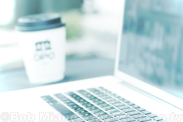 Photo of a laptop and coffee for online marketing of a startup incubator