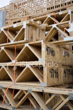 <a href=http://www.istockphoto.com/file_closeup/object/5687878.php?id=5687878&refnum=jwilkinson target=istock>Joists</a><br>a pile of wood joists (trusses) at a construction site, with framed walls in the background.