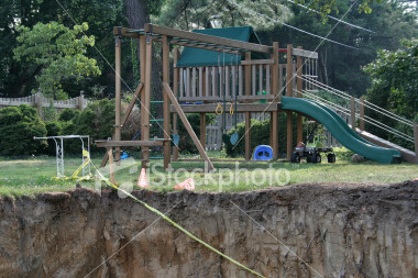 """<a href=""""http://www.istockphoto.com/file_closeup/object/1930705.php?id=1930705&refnum=jwilkinson"""" target=""""istock"""">Hole in a yard 2</a><br>looking up out of a large construction hole for a basement addition next to a green yard and home playset / swingset.<br><br>strong & abrupt visual fall-off from the nice family playset and green yard into the rough deep hole. <br><br>Themes can include: home improvement excavation, construction safety, safety at home, child safety, etc.<br><br>Or deeper themes such as how easy it is to go from a typical life(style) into various kinds of personal calamities (homelessness, financial debt, emotional problems...)<br><br>Themes could include: family financial debt, bankrupcy, emotional depression, down, in a hole, in a real mess, trapped, stuck, overwhelmed with problems, on the edge of ruin, etc.<br><br>One of a series, following this construction project.<br><br>See also: <br><a href=http://www.istockphoto.com/file_closeup.php?id=1930738><img border=0 src='http://www.istockphoto.com/file_thumbview_approve.php?size=1&id=1930738'></a> <a href=http://www.istockphoto.com/file_closeup.php?id=1930752><img border=0 src='http://www.istockphoto.com/file_thumbview_approve.php?size=1&id=1930752'></a> <a href=http://www.istockphoto.com/file_closeup.php?id=1930772><img border=0 src='http://www.istockphoto.com/file_thumbview_approve.php?size=1&id=1930772'></a> <a href=http://www.istockphoto.com/file_closeup.php?id=1974596><img border=0 src='http://www.istockphoto.com/file_thumbview_approve.php?size=1&id=1974596'></a> <a href=http://www.istockphoto.com/file_closeup.php?id=1974630><img border=0 src='http://www.istockphoto.com/file_thumbview_approve.php?size=1&id=1974630'></a> <br>"""