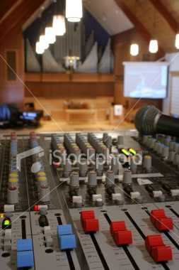 """<a href=""""http://www.istockphoto.com/file_closeup/object/3685085.php?id=3685085&refnum=jwilkinson"""" target=""""istock"""">Running sound at a church worship service</a><br>Peaceful view of a church sanctuary in soft focus behind a view of a sound/audio mixing board (console) and microphone.  Projection screen in background, with organ pipes and cross showing that it is a church. very sharp focus on the nearest sound board controls, with the service blurred by depth of field, though the center of the composition is the service & cross, not the tech. <br><br>Lighting is purposely brighter towards the front of the church vs that on the sound board, to emphasize the focus and purpose being there, not on the tech.<br><br>Concepts can include: running sound at church, the technical support behind services, the use of new technology in worship services & churches, etc. <br><br>See also: <br><a href=http://www.istockphoto.com/file_closeup.php?id=2191644&refnum=jwilkinson><img border=0 src='http://www.istockphoto.com/file_thumbview_approve.php?size=1&id=2191644'></a> <a href=http://www.istockphoto.com/file_closeup.php?id=2191493&refnum=jwilkinson><img border=0 src='http://www.istockphoto.com/file_thumbview_approve.php?size=1&id=2191493'></a> <a href=http://www.istockphoto.com/file_closeup.php?id=4551255&refnum=jwilkinson><img border=0 src='http://www.istockphoto.com/file_thumbview_approve.php?size=1&id=4551255'></a>"""