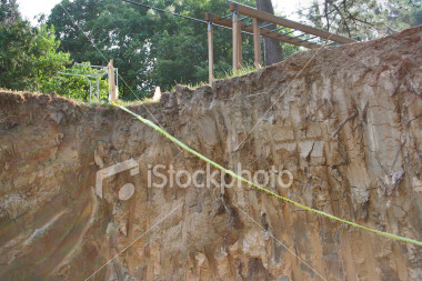 """<a href=""""http://www.istockphoto.com/file_closeup/object/1930772.php?id=1930772&refnum=jwilkinson"""" target=""""istock"""">In a real hole</a><br>looking up from a hole, a construction excavation for a basement<br><br>strong & abrupt visual fall-off from the nice family playset and green yard into the rough deep hole. <br><br>Themes can include: home improvement excavation, construction safety, safety at home, child safety, etc.<br><br>Or deeper themes such as how easy it is to go from a typical life(style) into various kinds of personal calamities (homelessness, financial debt, emotional problems...)<br><br>Themes could include: family financial debt, bankrupcy, emotional depression, down, in a hole, in a real mess, trapped, stuck, overwhelmed with problems, on the edge of ruin, etc.<br><br>One of a series, following this construction project.<br><br>See also: <br><a href=http://www.istockphoto.com/file_closeup.php?id=1930705><img border=0 src='http://www.istockphoto.com/file_thumbview_approve.php?size=1&id=1930705'></a> <a href=http://www.istockphoto.com/file_closeup.php?id=1930738><img border=0 src='http://www.istockphoto.com/file_thumbview_approve.php?size=1&id=1930738'></a> <a href=http://www.istockphoto.com/file_closeup.php?id=1930752><img border=0 src='http://www.istockphoto.com/file_thumbview_approve.php?size=1&id=1930752'></a>  <a href=http://www.istockphoto.com/file_closeup.php?id=1974596><img border=0 src='http://www.istockphoto.com/file_thumbview_approve.php?size=1&id=1974596'></a> <a href=http://www.istockphoto.com/file_closeup.php?id=1974630><img border=0 src='http://www.istockphoto.com/file_thumbview_approve.php?size=1&id=1974630'></a> <br>"""