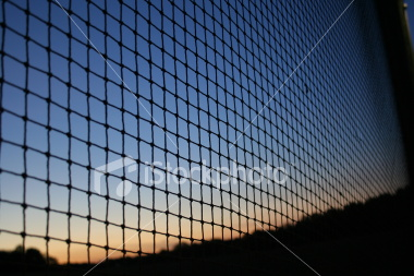 """<a href=""""http://www.istockphoto.com/file_closeup/object/4550797.php?id=4550797&refnum=jwilkinson"""" target=""""istock"""">Sunset sky through netting</a><br>A bold blue and orange sunset skyline silhouetted by netting running off at an angle in vanishing-point style.<br><br>very sharp focus and low-noise"""
