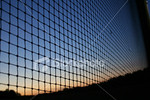 "<a href=""http://www.istockphoto.com/file_closeup/object/4550797.php?id=4550797&refnum=jwilkinson"" target=""istock"">Sunset sky through netting</a><br>A bold blue and orange sunset skyline silhouetted by netting running off at an angle in vanishing-point style.<br><br>very sharp focus and low-noise"