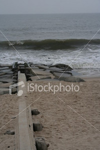 """<a href=""""http://www.istockphoto.com/file_closeup/object/1310662.php?id=1310662&refnum=jwilkinson"""" target=""""istock"""">beach break water</a><br>break water or piling and rock break to prevent surf rip currents, from Bethany Beach Delaware (what's this called?), cold, fall day, gray sky"""
