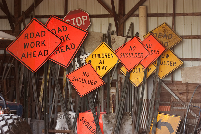 A group of road signs in a shed