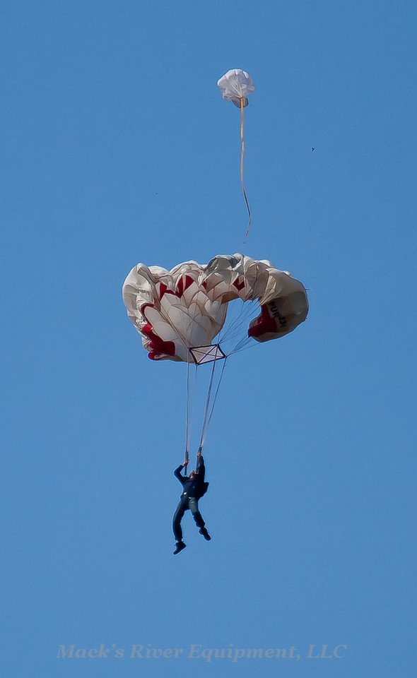 The main chute is inflating and the jumper is looking up to check it.