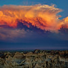 The last light of day colors a retreating storm over Badlands National Park in South Dakota.