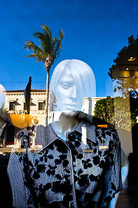 Reflection of Worth Ave. and a store mannequin.