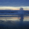 Oregon Coast.  A wave splashes off a rock as the wet sand reflects the sky.