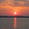 """Possum Kingdon Lake West of Fort Worth.  Actually this is a sunrise picture, and there are two """"paragliders"""" flying past the sun."""