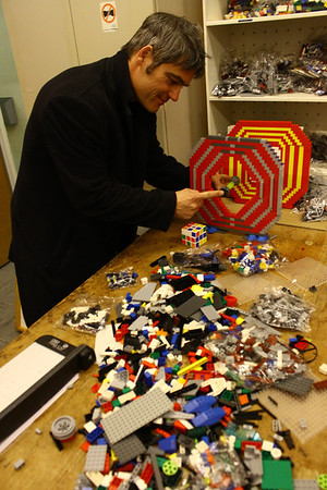 Physicist and unofficial in-house artist for CERN, Michael Hoch, building a replica of the Large Hadron Collider out of Legos. Photo by David Marks.