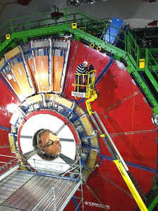"""Me filming crane shots of the CMS experiment, located in Cessy, France, which uses a general-purpose detector to investigate a wide range of physics, including the search for the Higgs boson (aka the """"God particle""""), extra dimensions, and particles that could make up dark matter. Although it has the same scientific goals as the ATLAS experiment, it uses different technical solutions and design of its detector magnet system to achieve these.  The following was written by my friend Ben Eshbach, who accompanied me on this trip:  """"Our first day of filming and interviewing at CERN brought us to one of the CMS detector.  The CERN ring is is 27 km in circumference and has four particle detectors at 12 o-clock, 4 o-clock, 6 o-clock and 8 o-clock. If you think of the visitor center (and the ATLAS detector in Meyrin, Switzerland) as being 6 o-clock then the CMS detector is at 12 o-clock. This meant that we had to drive across the French countryside to to get to it. Our contact person/driver was Fermilab's Kathryn Grim. Kathryn wasn't used to driving people around the French boondocks and so we drove in circles for a little while but it was fun. And beautiful. Part of our drive took us through the French commune of Ferney-Voltaire. This is where Voltaire wrote Candide. I personally found it exciting and ironic to be so close to the place where Pangloss and Martin were created. I would eventually encounter examples of Pangloss and Martin in my conversations at CERN. I'll return to Voltaire later.    When we arrived at CMS were each given small portable radiation detectors.  We grabbed hard-hats and were led through doors, past eye scanners, down tunnels and an elevator until we reached the room that housed the massive CMS detector.  This monster was asleep and dozens of Lilliputians were climbing on scaffolding around it with tools and various instruments. Its bright red and gold colors were truly impressive. I'll let the pictures speak for themselves. We were given just about """