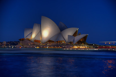 OH 105  Sydney, Australia, Opera House.  This is a night scene of the lighted building. The light streaks and reflections in the water are from ferry boats going in and out of Circular Quay during this time exposure.