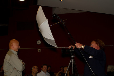 Using an umbrella with a small strobe to make an even larger effective source of light, softening the shadows