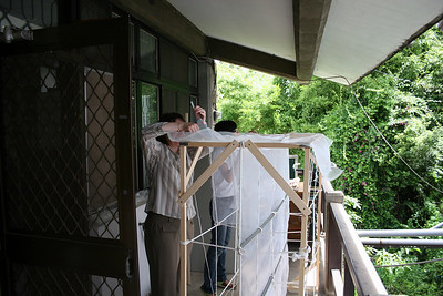 """Spider cage construction, very early in the process.  Wood was laid down and screwed together, PVC pipe tied down, and netting gluegunned by hand.  The gluegunning in particular was extremely tedious because you needed to close all holes to both outside and between adjacent """"cubes"""".  Nina became a master at this."""