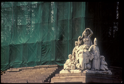 "Photograph of the Albert Memorial being restored in the early 1990s, enveloped in scaffolding and green mesh apart from the statue group representing ""Asia""."