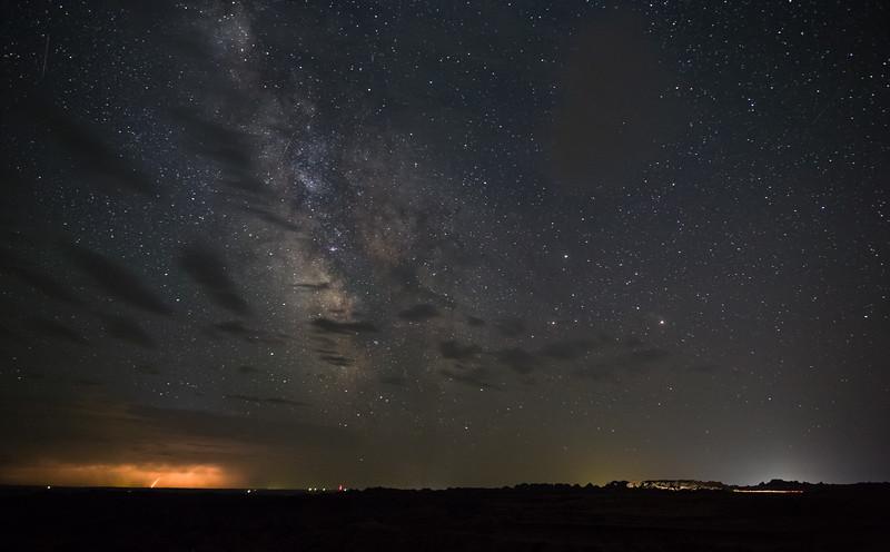Lightning , Milky Way and car lights in the South Dakota Badlands