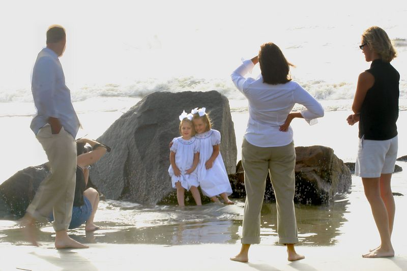 Children hold dresses up in surf<br> while posing for their photo