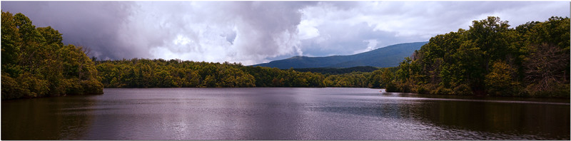 Jul 26<br /> A calm lake nestled in the mountains of NC<br /> <br /> Driving along the highway in the mountains. we stopped to grab this shot of the mountains and lake.