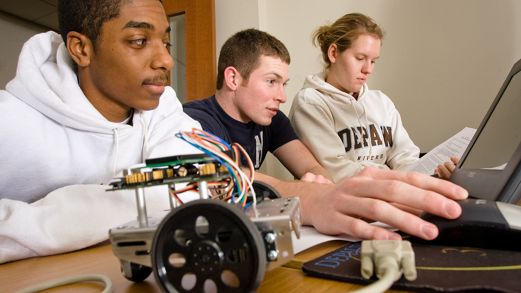 Freshmen Naiquan Greene, Alan Dull, and Sara Ketterer program a robot (foreground) in Computer Science on Wedneday. Photo by Alex Turco